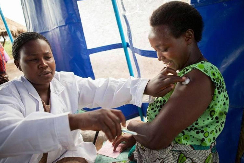 a nurse giving a woman a vaccine shot