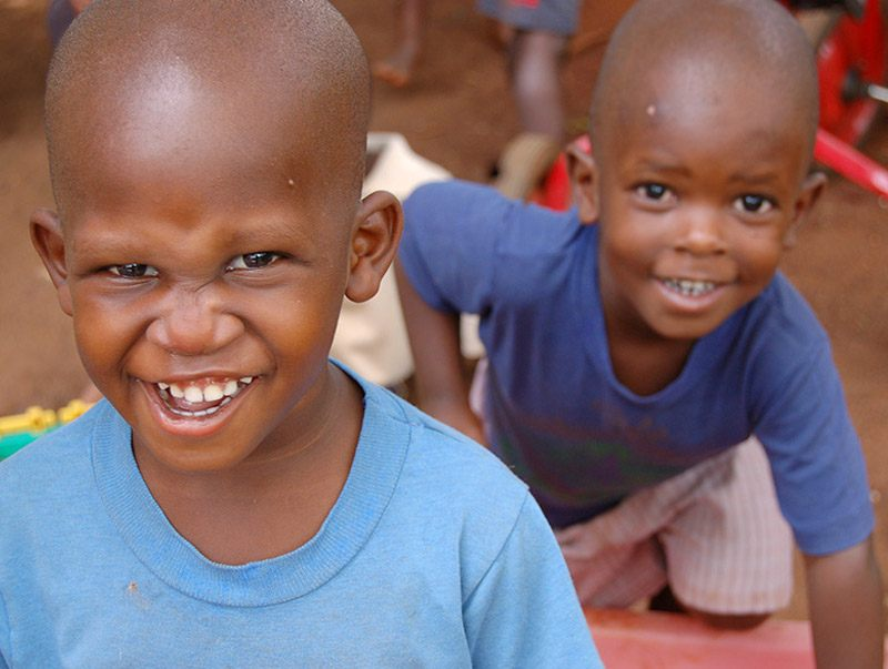 two young boys smiling and getting their picture taken while playing