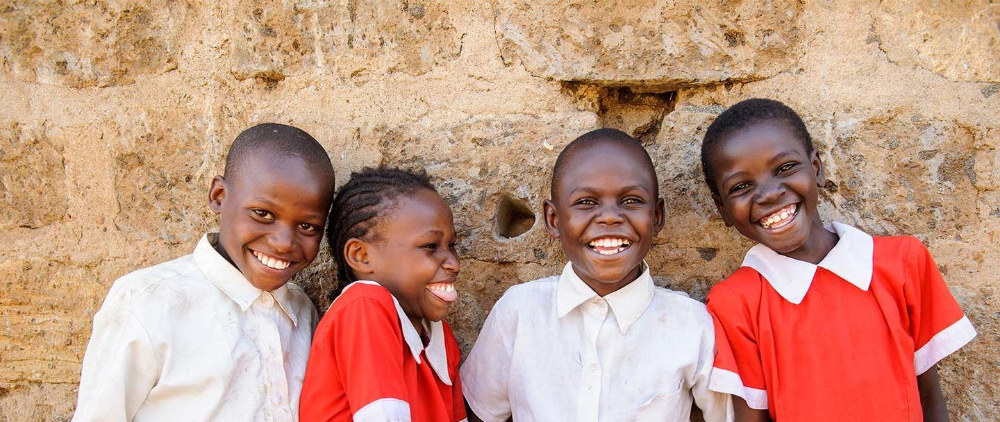 four young children in a developing country dressed in matching red and white clothes smiling and laughing