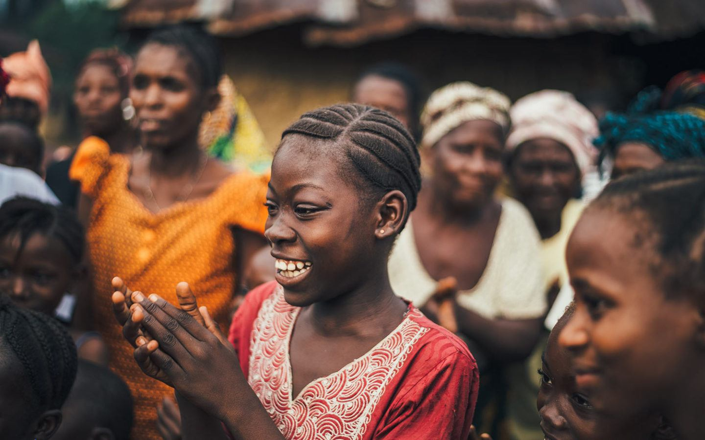 a group of young women smiling and clapping in a developing country