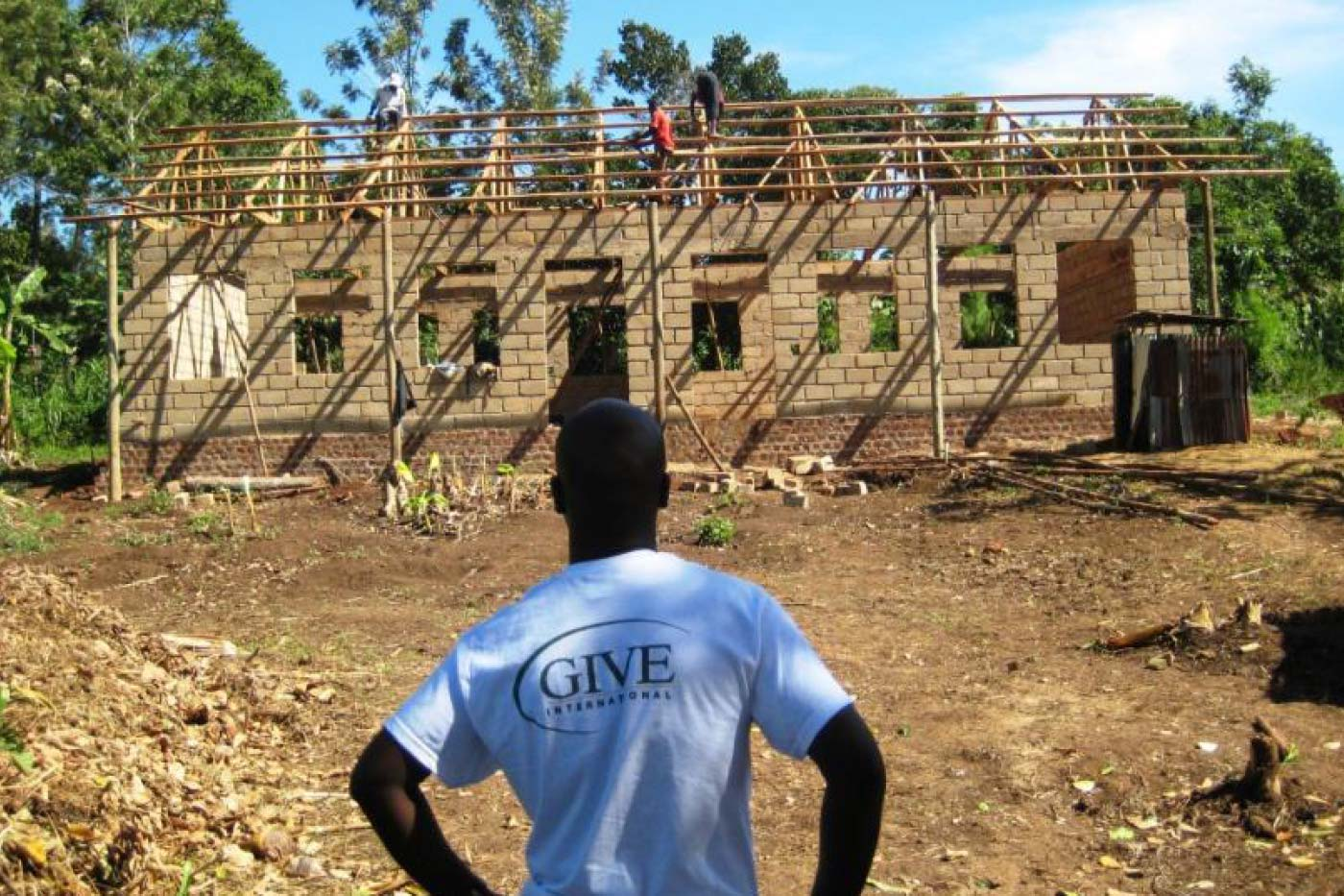 a volunteer watching a building construction in a developing country