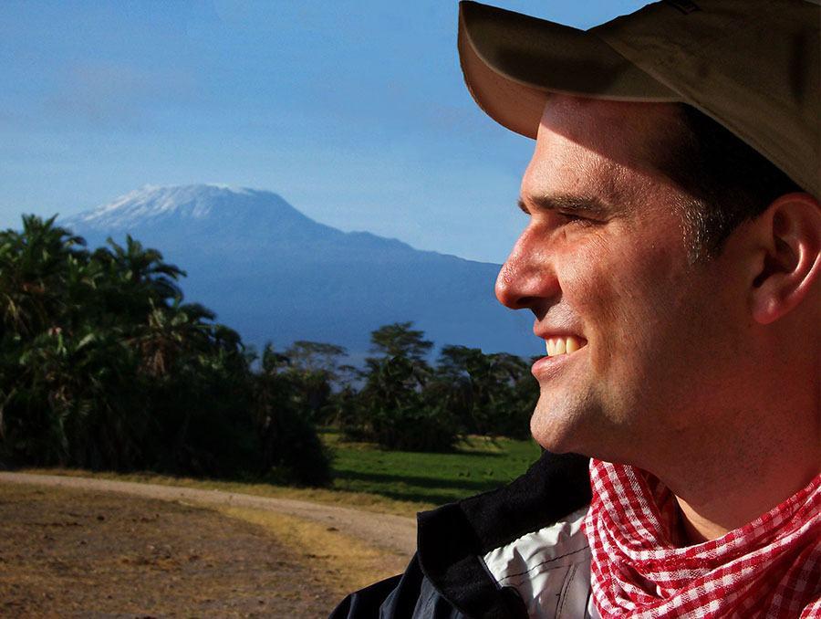 Ryan Snider posing and smiling by Kilimanjaro
