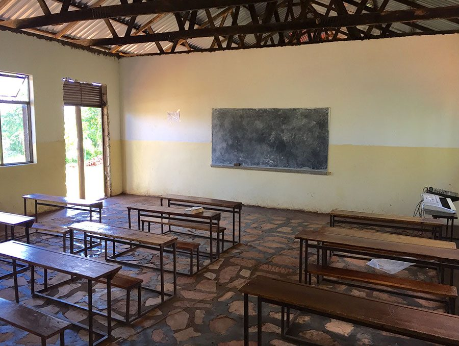 a classroom with desks and chalkboard wall in a developing country