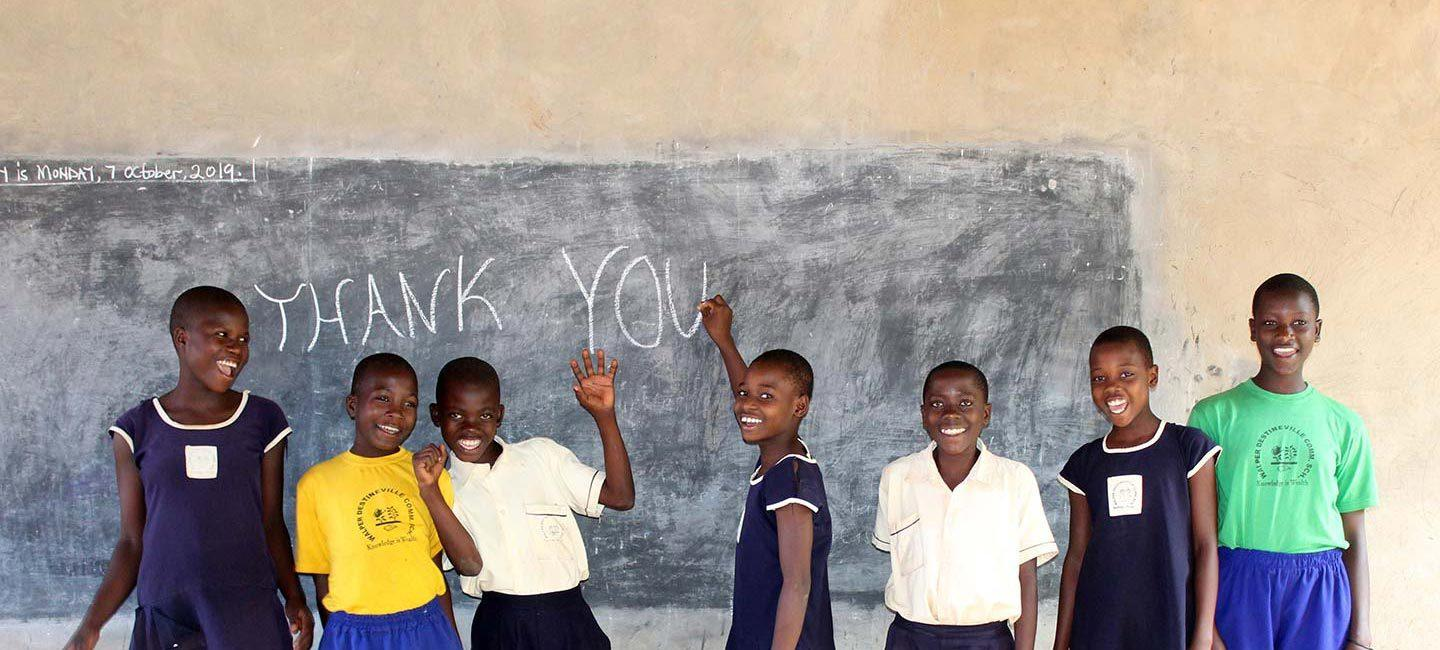 "a group of young boys standing in front of a chalkboard wall with the words ""thank you"" written on it"