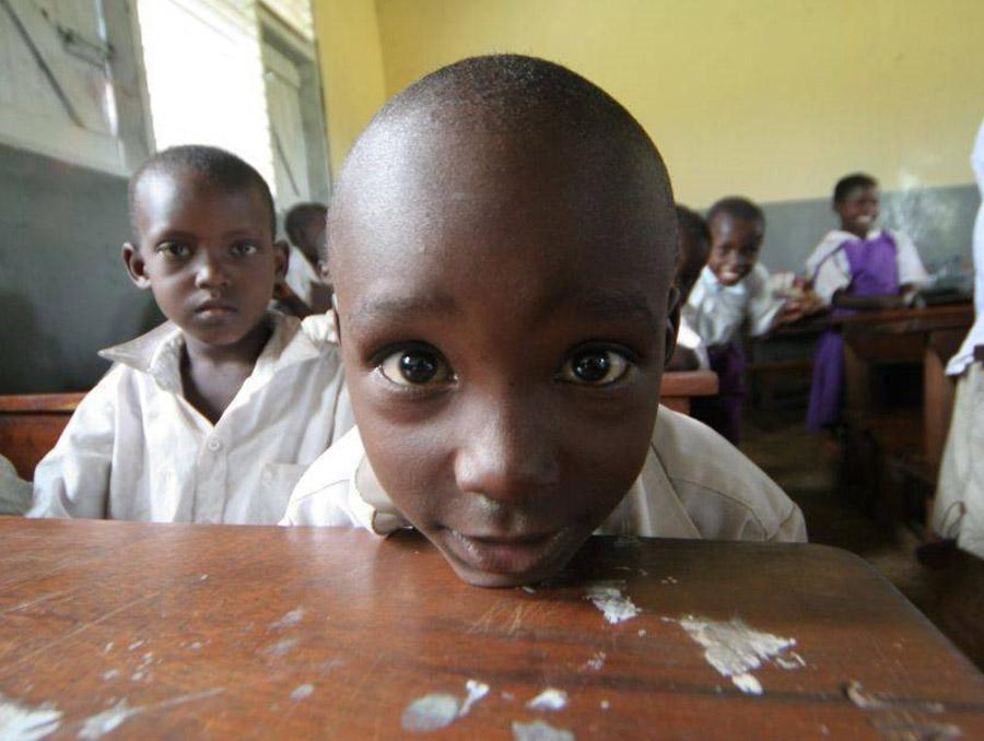 two young boys sitting at their desk in a classroom in a developing country