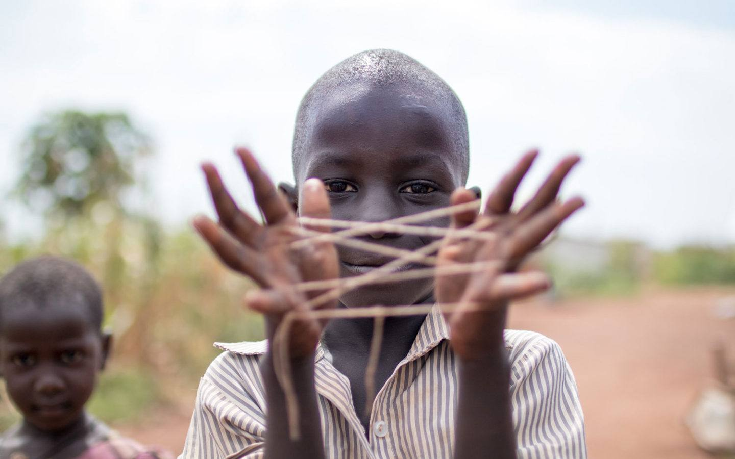 a young boy in Kenya showing a web of string stretched out between his hands