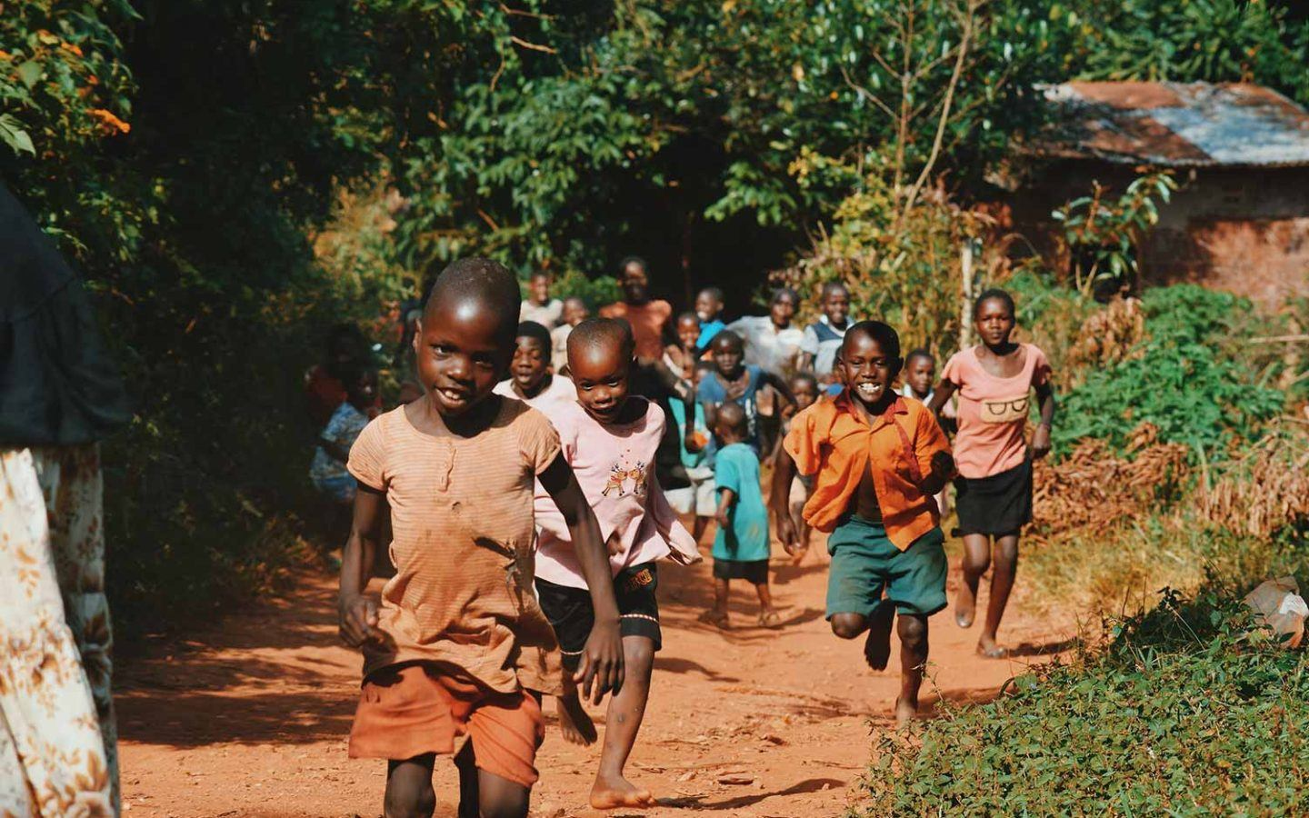 a group of young children in Kenya running down a path and smiling