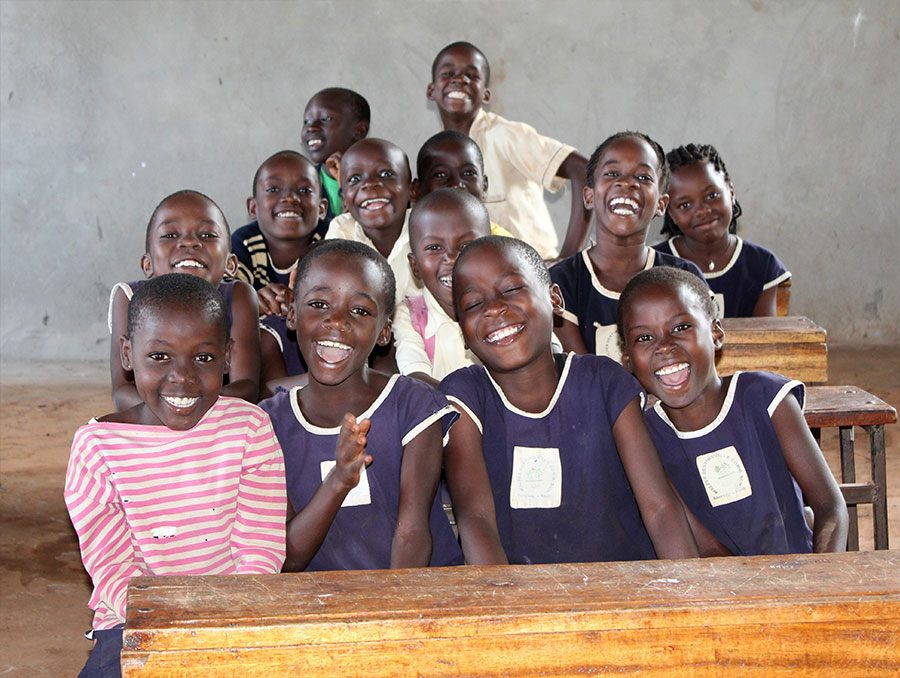 a group of school-age children in a developing country classroom sitting together at a desk and smiling