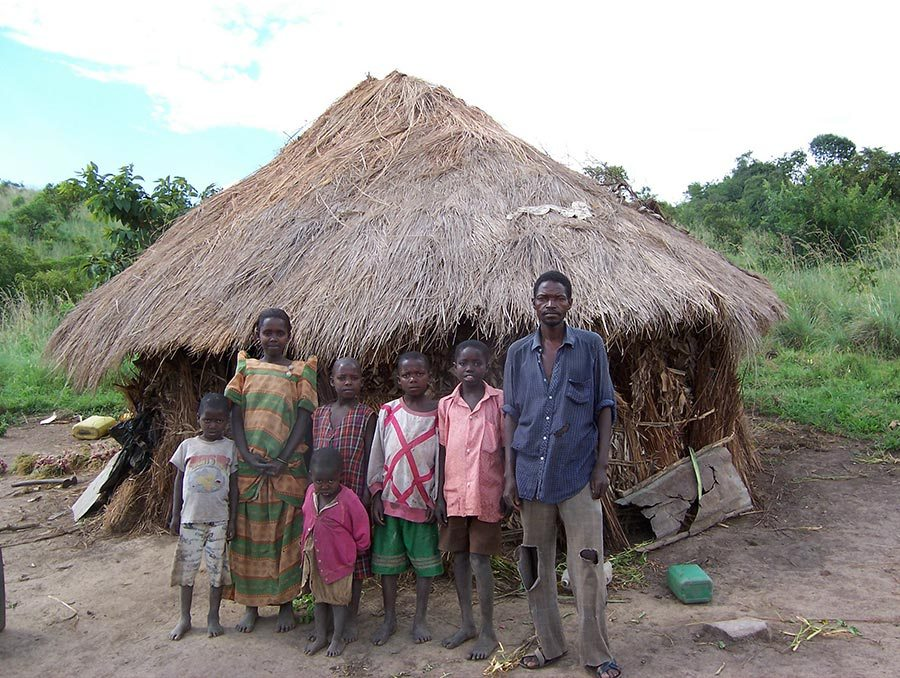 a family with a man, woman, and 5 children standing in front of a straw hut in a developing country