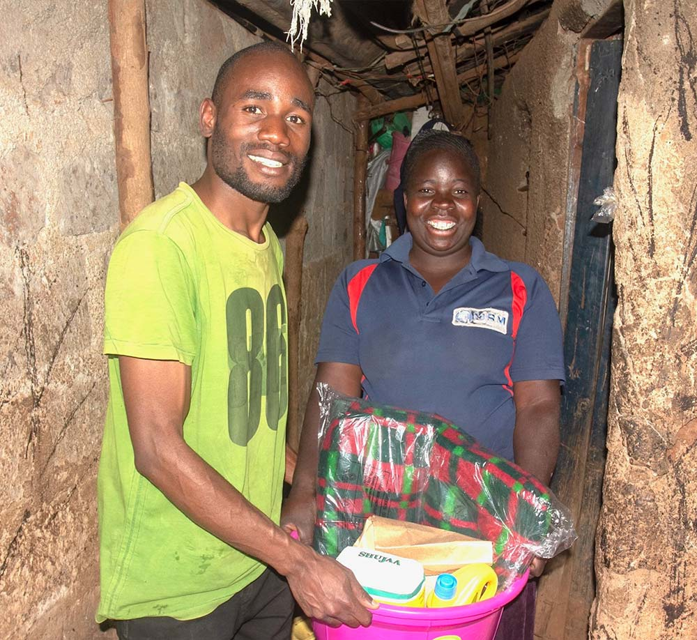 two people holding a container of household supplies for an international support program in Kenya